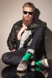 Manlig modell för mode i sammanträde för läderomslag royaltyfri bild
