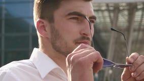 Manlig modell för stiligt mode som av tar hans solglasögon och blickar till kameran Stads- stadsbakgrund lager videofilmer