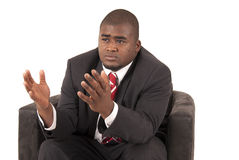 Manlig modell i affärsdräkt och rött randigt bandsammanträde i stol Fotografering för Bildbyråer