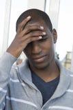 Manlig modellhand för afrikansk amerikan på huvudet som tänker eller grubblar Arkivfoto