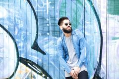 Manlig modemodell med solglasögon som poserar vid grafitti Royaltyfri Fotografi
