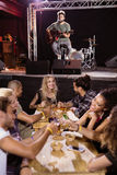 Manlig musiker som sjunger med fans som sitter på tabellen Royaltyfria Foton