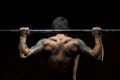 Manlig muskulös idrottsman nen som gör övre övning för handtag royaltyfri fotografi