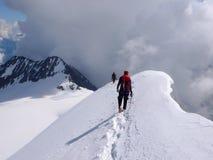 Manlig och kvinnlig bergsbestigare som stiger ned från en hög alpin toppmöte längs en smal snö- och iskant fotografering för bildbyråer