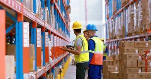 Manlig och kvinnlig lagerarbetare som kontrollerar materielet stock video