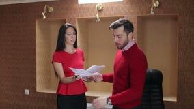 Manlig och kvinnlig utövande diskuterande rapport med kontorsmöte stock video