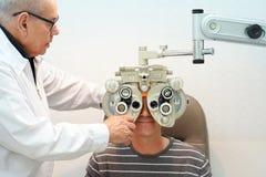 Manlig optometriker Doing Sight Testing för den manliga patienten i klinik royaltyfria bilder