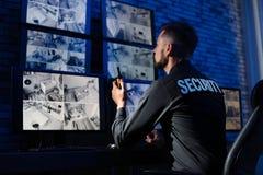 Manlig ordningsvakt med den bärbara sändaren som övervakar moderna CCTV-kameror arkivfoton