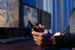 Manlig ordningsvakt med den bärbara sändaren som inomhus övervakar moderna CCTV-kameror royaltyfri bild