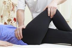 Manlig osteopat som behandlar den kvinnliga patienten med höftproblem Royaltyfri Fotografi