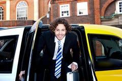 Manlig passanger som får ut ur en taxitaxi Fotografering för Bildbyråer