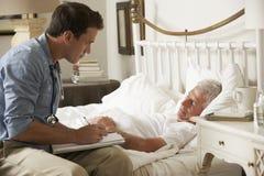 Manlig patient för doktor Talking With Senior i säng hemma royaltyfri bild