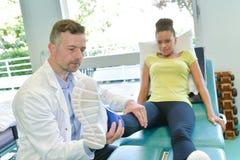 Manlig patient för fysioterapeutprovningsben i physio rum arkivbild