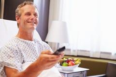 Manlig patient i hållande ögonen på television för sjukhussäng royaltyfria bilder