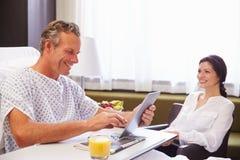 Manlig patient i sjukhussäng genom att använda den Digital minnestavlan Arkivfoton