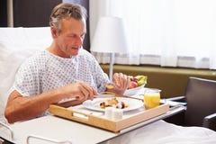 Manlig patient i sjukhussäng som äter mål från magasinet royaltyfria bilder