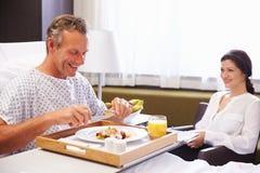 Manlig patient i sjukhussäng som äter mål från magasinet royaltyfria foton