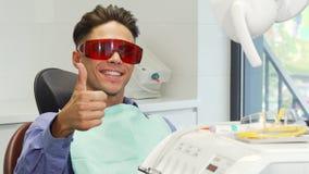 Manlig patient som bär skyddande exponeringsglas som visar upp tummar på tandläkarekontoret arkivfoto