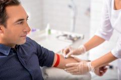 Manlig patient som har blodprovtagningen royaltyfria bilder