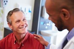Manlig patient som uppmuntras av doktor In Hospital Room arkivbilder