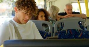 Manlig pendlare som använder den digitala minnestavlan, medan resa i bussen 4k arkivfilmer