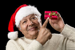 Manlig pensionär med den röda Pompomhatten och julgåvan Arkivbilder