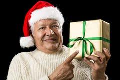 Manlig pensionär med den Santa Cap Pointing At Golden gåvan Royaltyfri Fotografi