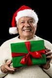 Manlig pensionär med Santa Claus Cap och den gröna gåvan royaltyfria bilder