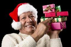 Manlig pensionär som pekar fast på sex slågna in gåvor Royaltyfria Bilder