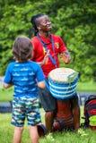 Manlig percussionist för afrikansk amerikan som spelar rytm med hans djembevalsbongo arkivfoton