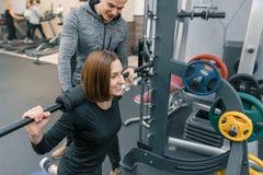 Manlig personlig konditioninstruktör som hjälper den unga kvinnan att göra genomkörare i idrottshall Sport, idrottsman nen, utbil royaltyfria foton