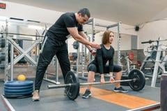 Manlig personlig konditioninstruktör som hjälper den unga kvinnan att göra genomkörare i idrottshall Sport, idrottsman nen, utbil arkivfoto