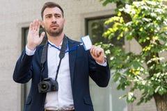 manlig photojournalist med den digitala fotokameran som gör en gest och visar royaltyfri bild
