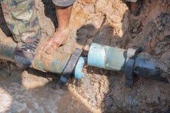 Manlig pik för arbetare ett hål som fixar vattenläckan på stort på vägen royaltyfria bilder