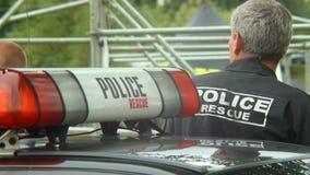 Manlig polis i laddningshändelsen som säkrar, säkerhetsvakt, arbetsuppgift lager videofilmer