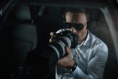 manlig privat kriminalare i hörlurar som gör bevakning vid kameran med objektexponeringsglas royaltyfri fotografi