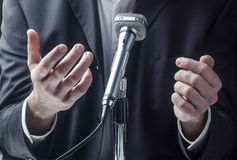 Manlig professionell som talar en framdel av en allmänhet med en micro Fotografering för Bildbyråer