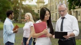 Manlig professor som diskuterar tes med den asiatiska kvinnliga studenten nära universitet arkivfoton