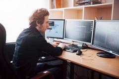 Manlig programmerare som arbetar på den skrivbords- datoren med många bildskärmar på kontoret i programvara för att framkalla för arkivbild