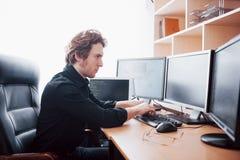 Manlig programmerare som arbetar på den skrivbords- datoren med många bildskärmar på kontoret i programvara för att framkalla för arkivfoton