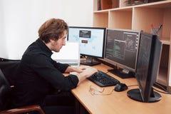 Manlig programmerare som arbetar på den skrivbords- datoren med många bildskärmar på kontoret i programvara för att framkalla för royaltyfri fotografi
