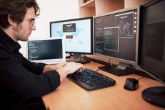 Manlig programmerare som arbetar på den skrivbords- datoren med många bildskärmar på kontoret i programvara för att framkalla för arkivfoto