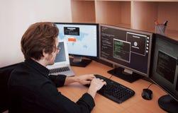 Manlig programmerare som arbetar på den skrivbords- datoren med många bildskärmar på kontoret i programvara för att framkalla för arkivbilder