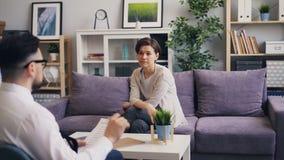 Manlig psykolog som i regeringsst?llning talar till den n?tta patienten f?r ung kvinna under period arkivfilmer
