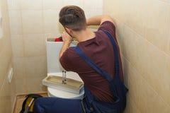 Manlig r?rmokare som reparerar toalettbeh?llaren royaltyfri bild