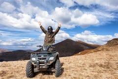 Manlig ryttare på ATV på bergöverkanten Royaltyfri Bild