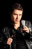 Manlig sångare som rymmer en mikrofon Arkivbild