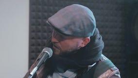 Manlig sångare som sjunger känslomässigt en sång i mikrofon stock video