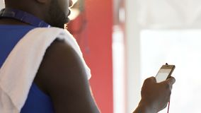 Manlig sökande efter kontakt av vännen på mobiltelefoninställningstidsbeställning efter idrottshall lager videofilmer