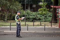 Manlig serbisk polis i likformig som skriver en biljett i Belgrade Han tillhör civilpolisstyrkan av landet royaltyfria bilder